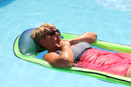 lilo: An english lady relaxing in a swimming pool while on vacation