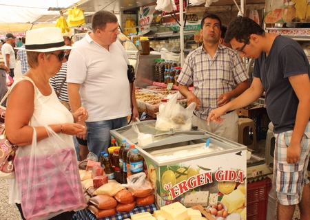 travelling salesman: CALIS, TURKEY,JULY 2015: English tourists buying fresh yogurt and cheese from a trader at a local turkish market in calis,july 2015