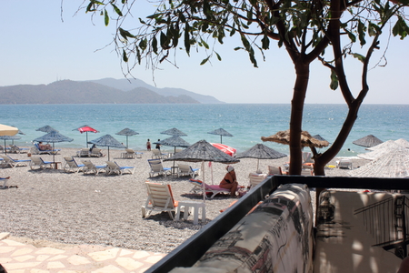 turkey beach: CALIS, TURKEY, JULY 2015: Sunbeds and umbrellas at Calis beach in Turkey,2015 Editorial