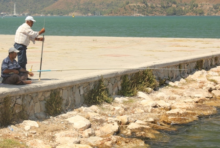 unknown men: FETHIYE, TURKEY, 21ST JULY 2015: Two unknown turkish men fishing in the sea at fethiye in turkey, 21st july 2015 Editorial