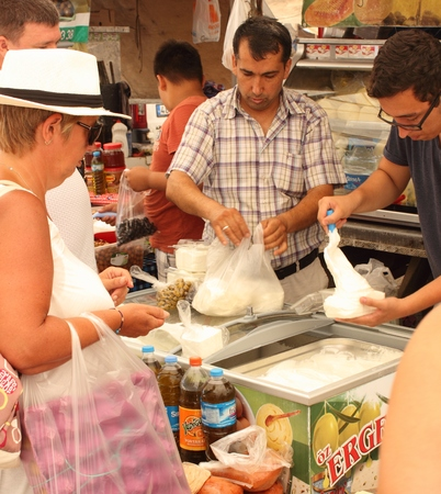 travelling salesman: CALIS, TURKEY,JULY 2015: An English tourist buying fresh yogurt and cheese from a trader at a local turkish market in calis,july 2015