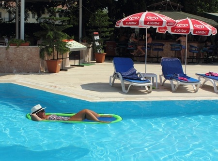 lilo: CALIS, TURKEY, 2ND AUGUST 2015:An english Lady relaxing  in a swimming pool while on holiday in calis, turkey ,2nd august 2015