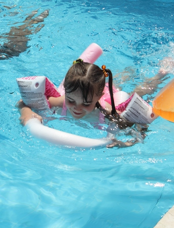 armbands: CALIS, TURKEY, 2ND AUGUST 2015: A young English girl wearing a hat and using armbands swimming in a pool while on vacation in calis in turkey on the 2nd august 2015