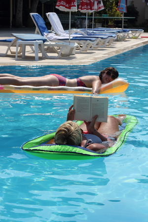lilo: CALIS, TURKEY, 2ND AUGUST 2015:An english Lady relaxing and reading a book in a swimming pool while on holiday in calis, turkey ,2nd august 2015
