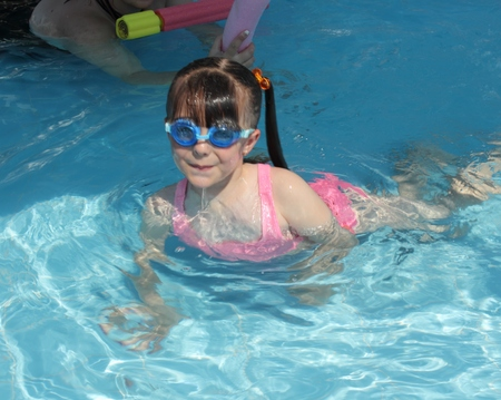 english girl: CALIS, TURKEY, 2ND AUGUST 2015: A young English girl wearing goggles and swimming in a pool while on vacation in calis in turkey on the 2nd august 2015 Editorial