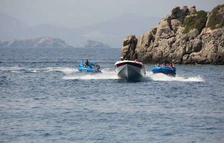 speedboats: FETHIYE, TURKEY, 27TH JULY 2015: Tourists having fun riding in inflatables being pulled by a speedboat in a bay at Fethiye ,Turkey, 27th july 2015 Editorial