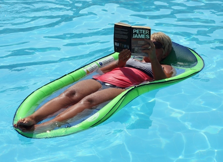 lilo: An english lady relaxing and reading a book in a swimming pool while on vacation