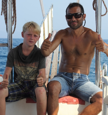 turkish man: A turkish man aboard a boat with an english boy in turkey, 1st august 2015
