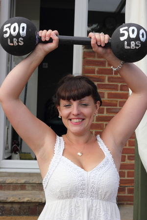 gym dress: A young lady lifting some fake heavy weights above her head