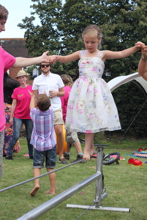 helpers: 22ND AUGUST 2015, A young girl learning to tightrope walk and being assisted by helpers in an english garden in portsmouth on the 22nd august 2015