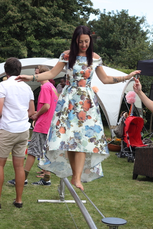 assisted: 22ND AUGUST 2015, An english lady  learning to tightrope walk and being assisted by helpers in an english garden in portsmouth on the 22nd august 2015