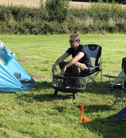 fire pit: PETWORTH, ENGLAND, 29TH AUGUST 2015: An unknown man camping and sitting next to a fire pit in a field in petworth, england, 29th august 2015