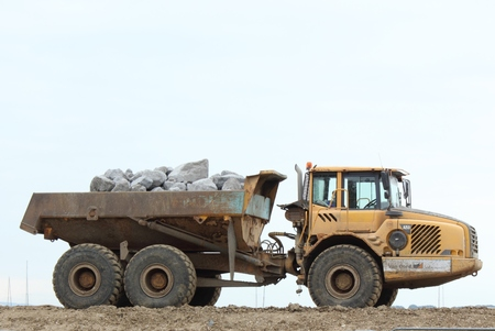 september 9th: PORTSMOUTH, ENGLAND, 9TH SEPTEMBER 2015: A large tipper lorry carrying and delivering large rocks for the construction industry in Portsmouth, England, 9th September 2015