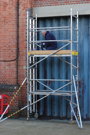 scaffold: A painter and decorater working from a scaffold tower