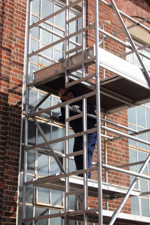 A Painter And Decorator Working From A Scaffold Tower Stock Photo ...