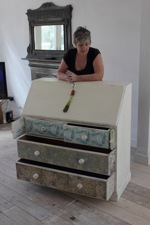 bureau: An artist painting and distressing a bureau in her studio, 2016