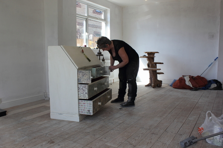 distressing: An artist painting and distressing a bureau in her studio, 2016