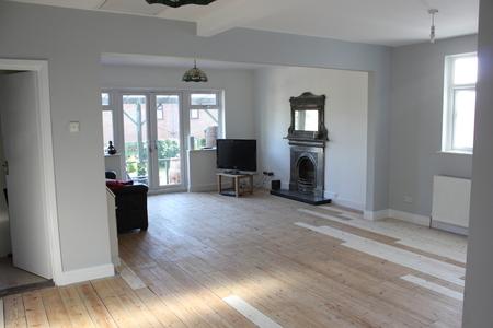 Ein Moderner Wohnbereich mit weißen Wänden und Dielen dekoriert fertig lackiert werden