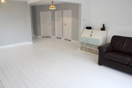 A Contemporary living area being decorated with white walls and floorboards