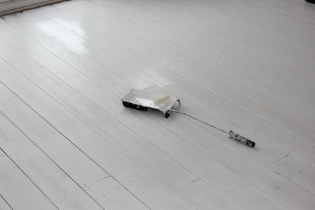 floorboards: A roller and paint tray on newly painted white floorboards