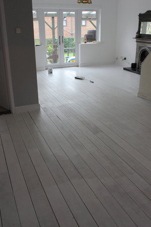 floorboards: A Contemporary living area being decorated with white walls and floorboards