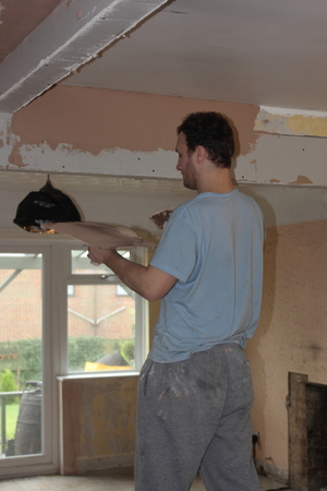 skimming: PORTSMOUTH, ENGLAND, 14th MARCH 2016:  A plasterer plastering walls and ceilings for a smooth finish in a house in portsmouth, england, 14th march 2016