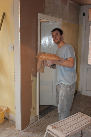 skimming: PORTSMOUTH, ENGLAND, 14th MARCH 2016:  A plasterer plastering walls for a smooth finish in a house in portsmouth, england, 14th march 2016 Editorial
