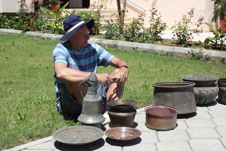he old: 28TH MAY 2016, CALIS, TURKEY : An Englishman with his purchase of old antique copper pots which he bought in Calis in Turkey, 28th may 2016