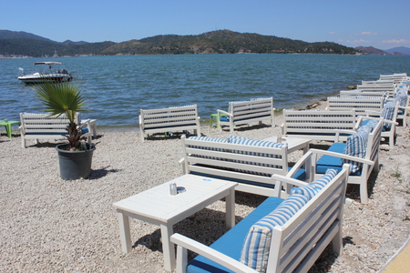 seating area: FETHIYE, TURKEY, 27TH MAY  2016:A restaurants seating area with boating in the background along the promenade in Fethiye, Turkey, 27th may 2016 Editorial