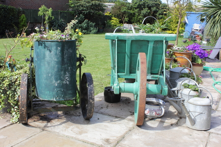 planters: An english garden with a vintage water carrier and wheel barrow being used as planters for flowers