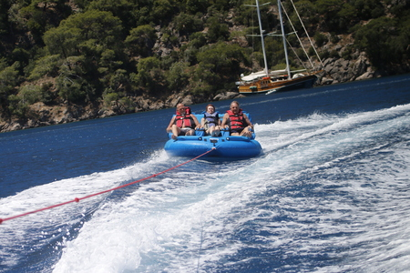 speedboat: English tourists having fun riding in inflatables being pulled by a speedboat in a bay at Fethiye ,Turkey, 25th may 2016 Editorial