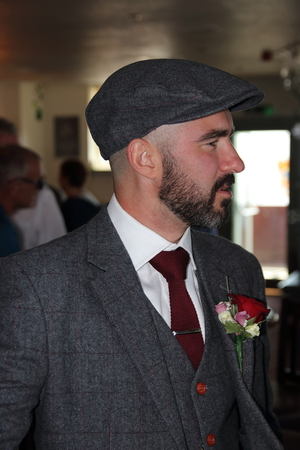 blinder: A groom at his wedding with a floral button hole and wearing a flat cap, 2016