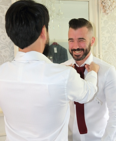 get dressed: 2ND JULY 2016, PORTSMOUTH,ENGLAND: A bestman helping the groom get dressed for his wedding in portsmouth, england, 2nd july 2016