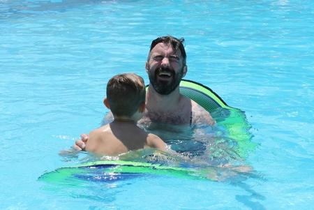 A father with his young son in a swimming pool while on vacation, 2016