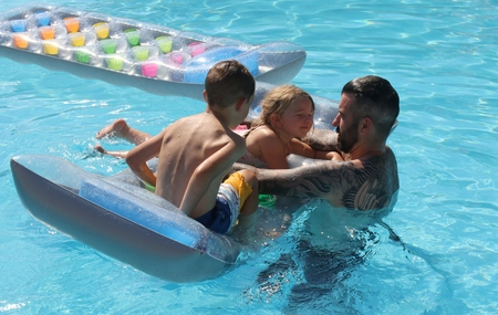A father with his two young children in a swimming pool while on vacation, 2016
