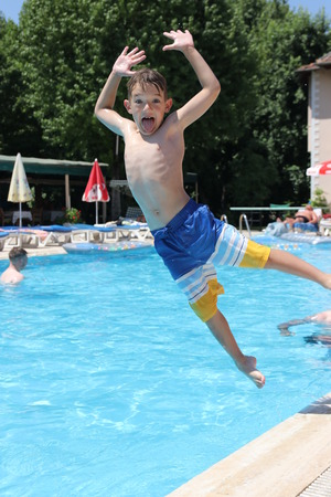 armbands: 14TH JULY 2016,CALIS,TURKEY; A young boy jumping into a swimming pool while on vacation in Calis in Turkey,14th july 2016 Editorial