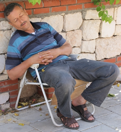 asleep chair: 17TH JULY 2016, CALIS,TURKEY: An unknown turkish male asleep in a chair during the summertime at calis in turkey, 17th july 2016