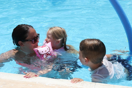 17TH JULY 2016,CALIS,TURKEY:A mother and her young children having fun in a swimming pool while on vacation in calis in turkey,17th july 2016 Stock Photo