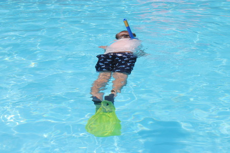 A young boy snorkeling in a swimming pool while on vacation, 2016