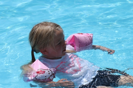 armbands: 18TH JULY 2016, CALIS, TURKEY; A young girl wearing armbands as floatation aids in a swimming pool while on vacation in calis, turkey, 18th july 2016 Stock Photo
