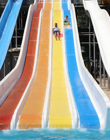 A father and son having fun on a water slide in a waterpark while on vacation in turkey