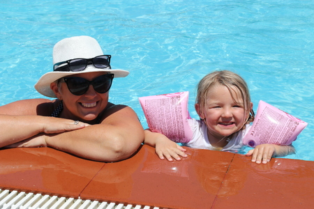 grand daughter: A grandmother with her grand daughter in a swimming pool while on vacation