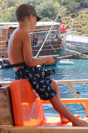 A young boy fishing from a boat while on vacation in turkey 2016 photo