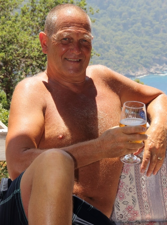 An englishman relaxing in the sunshine with a drink while on vacation, 2016 photo