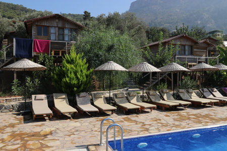 sunbeds: A relaxing area with sunbeds and umbrellas around a pool at Kabak in Turkey, 2016