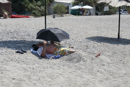turkish man: 31ST JULY 2016,CALIS, TURKEY; A local turkish man laying in sand under an umbrella and under a second umbrella  along Calis beach in Turkey,31st july 2016