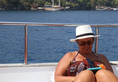 fethiye: An english lady relaxing while on a boat trip around the bays at fethiye in turkey, 2016