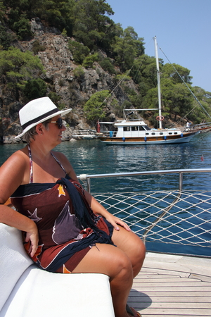 adulthood: An english lady relaxing while on a boat trip around the bays at fethiye in turkey, 2016
