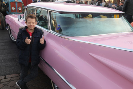 hants: 26TH DECEMBER 2016,WICKHAM,HANTS: A young boy with his thumbs up while standing next to an old retro car at a classic car show in wickham, england on the 26th december 2016