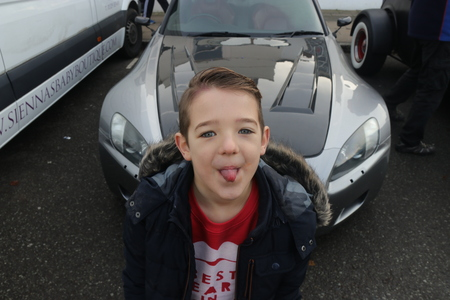 26TH DECEMBER 2016,WICKHAM,HANTS: A young boy with his tongue out while standing next to an old retro car at a classic car show in wickham, england on the 26th december 2016